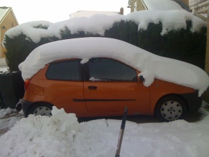 Orange car under 4 foot of snow