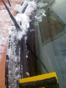 Clear snow from windscreen wipers with a scraper