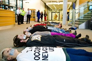 Protesters lie in a line with gaffer-taped mouths