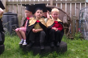 Children dressed in graduation gowns and motor boards